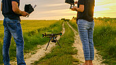 Men and woman using remote devices near standing drone