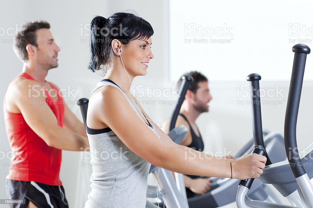 Men and woman working out on elliptical cross trainer at gym royalty-free stock photo