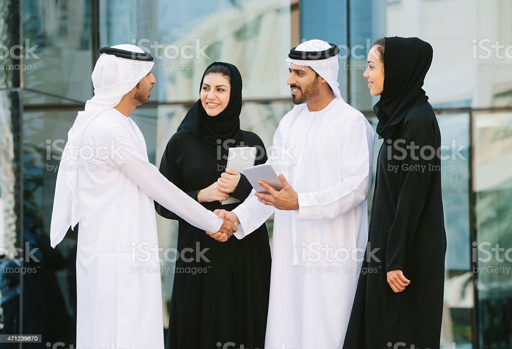 Middle eastern businesspeople shaking hands in front of an office...