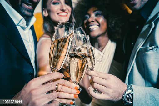 istock Men and women celebrating party while clinking glasses with sparkling wine 1055924044