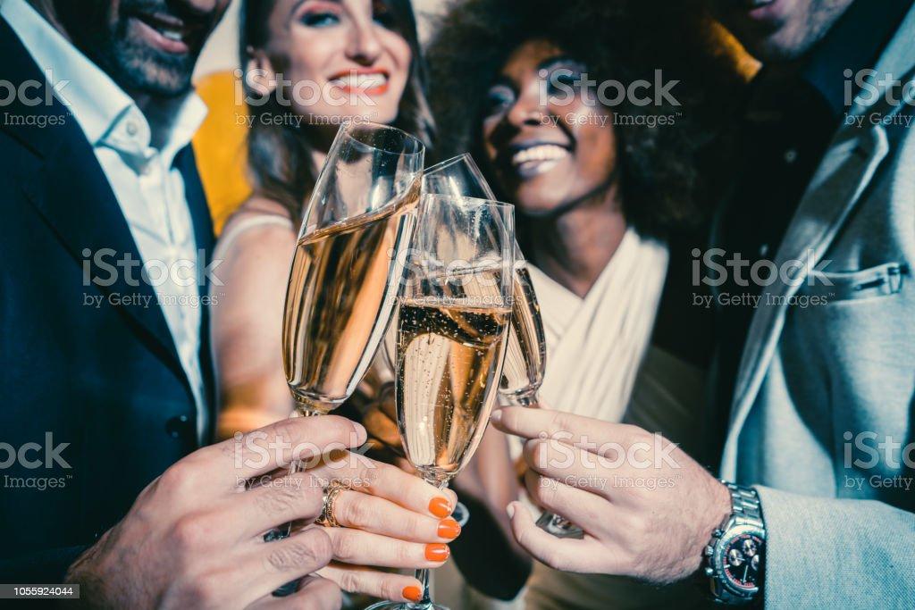 Männer und Frauen feiern Party während klirrende Gläser mit Sekt – Foto