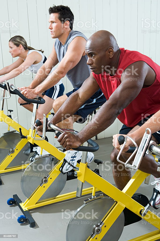 Men and women cycling on exercise bikes royalty-free 스톡 사진