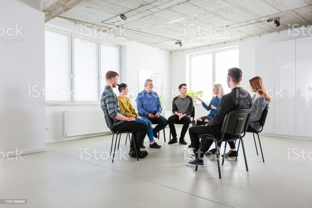 Men and women discussing problems in lecture hall Young students sharing their problems with mental health professional. Group of people are having discussion in lecture hall. They are sitting on chairs. 18-19 Years Stock Photo