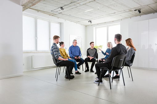 Men And Women Discussing Problems In Lecture Hall Stock Photo - Download Image Now
