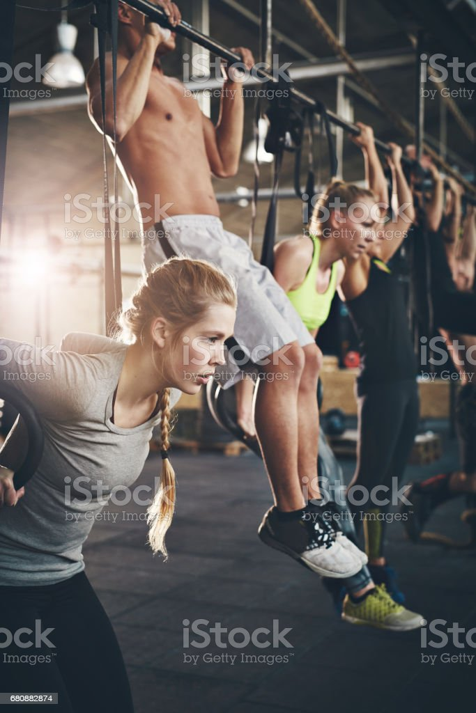 Men and women doing pull ups on bar in gym stock photo