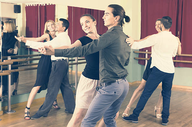 men and women enjoying of tango in class - dance class stock photos and pictures