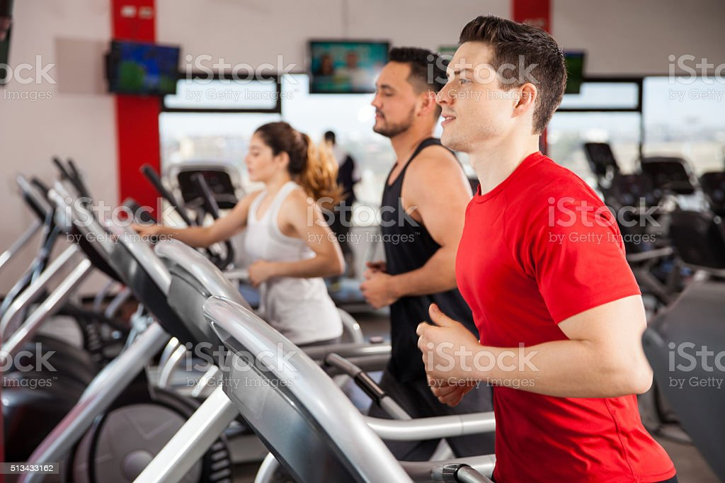 Men and women jogging on a treadmill stock photo