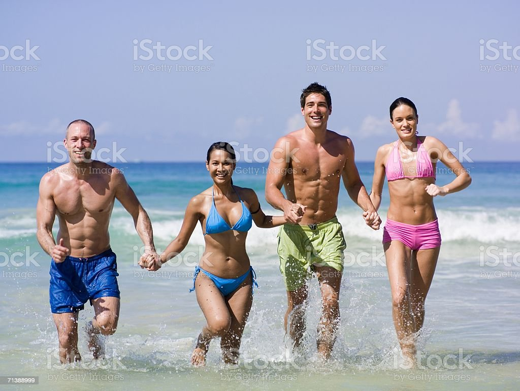 Men and women running in the sea royalty-free stock photo
