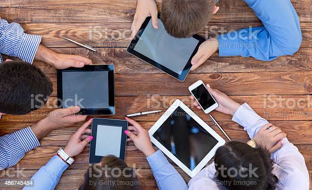 Men And Women Staring Intensively On Screens Of Digital Gadgets Stock Photo - Download Image Now