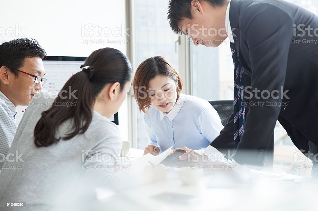 Men and women to see the smart phone in office stock photo