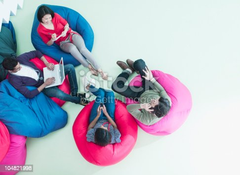 istock Men and women using laptop and cell phones in bean bag chairs 104821998