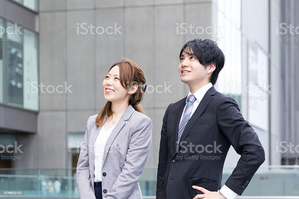 Men and women who look up to sky (business image) ストックフォト