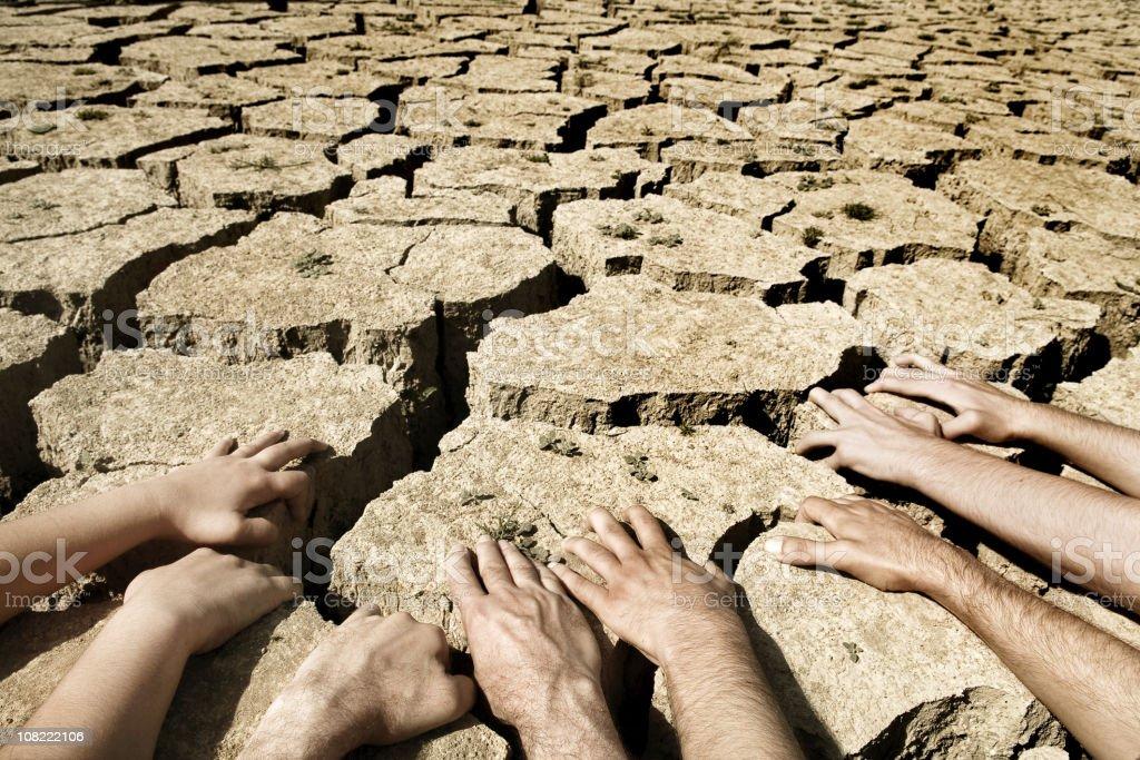 Men And Womens Hands Resting On Arid Desert Soil Stock ...