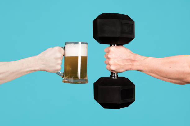 Los hombres se están sosteniendo un vaso de cerveza y una mancuerna grande - foto de stock