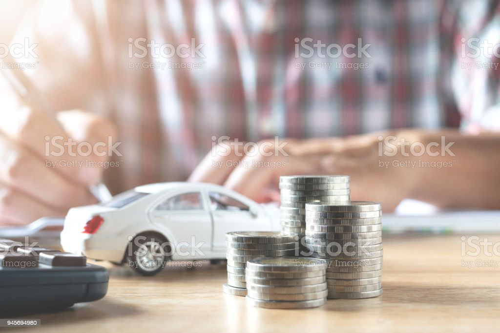 Men are Saint documents about cars  with  some coins calculator and car toy on desk. stock photo