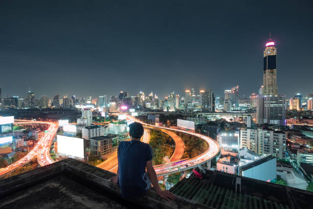 Men are sitting on balcony with sightseeing the city glowing at night stock photo