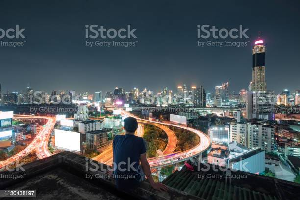 Photo of Men are sitting on balcony with sightseeing the city glowing at night