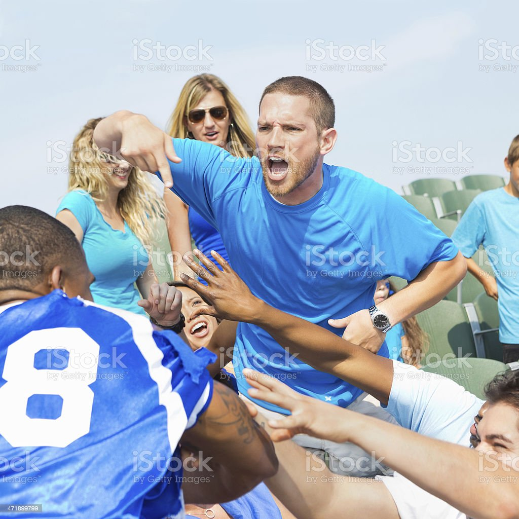 Men arguing and fighting during sporting event in stadium stock photo
