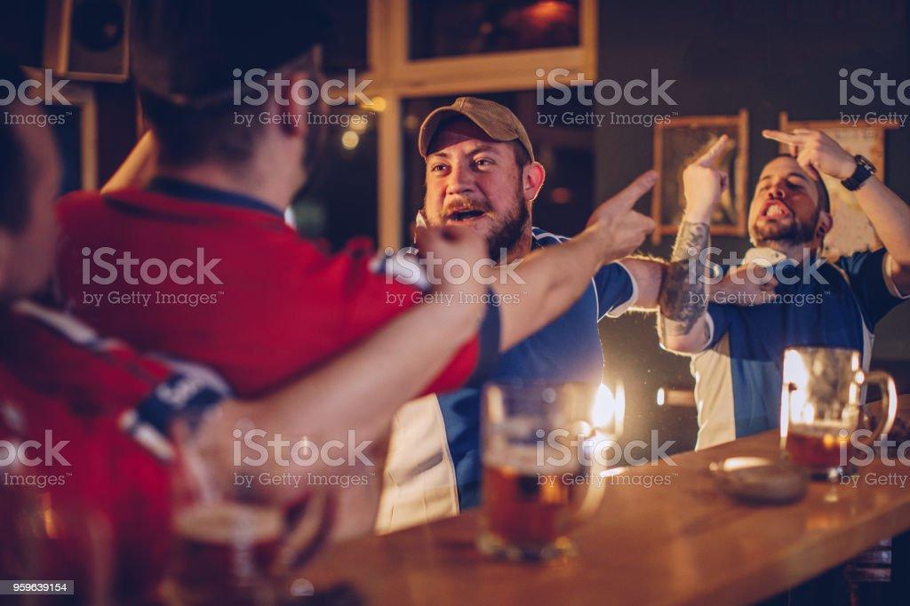 Hombres discutiendo en pub - Foto de stock de Aclamar libre de derechos