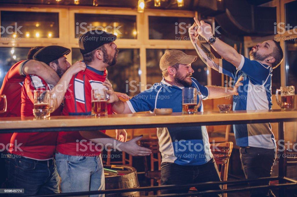 Men arguing in sports pub stock photo