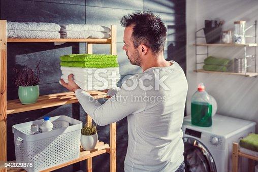 istock Men arranging clean towels at laundry room 942029378