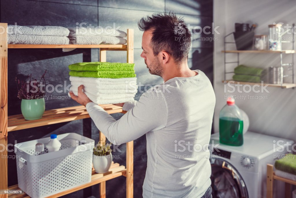 Men arranging clean towels at laundry room stock photo