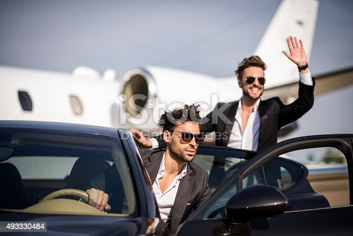 Two young well dressed men with sunglasses arriving at the airport and exiting from black SUV. The man in the back is waving to someone. Private airplane is in the background.