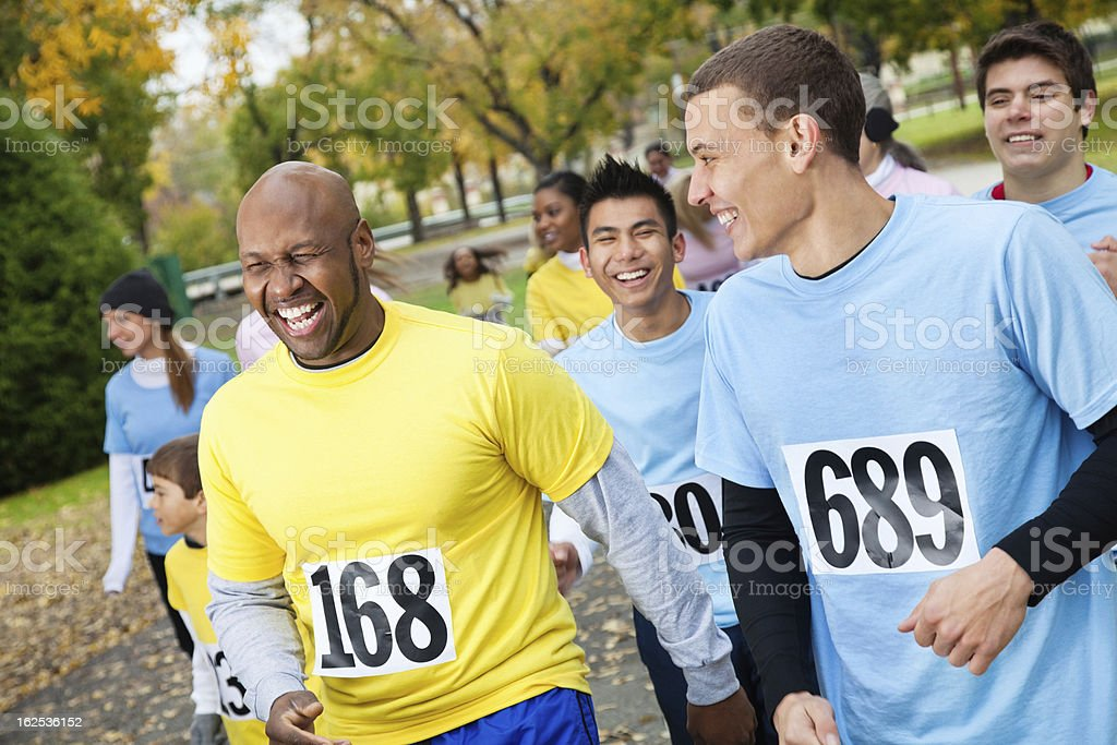 Men at a charity race laughing together stock photo