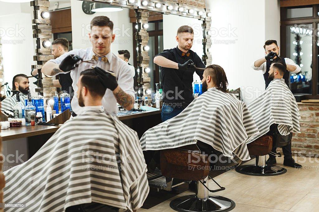 Men at barber shop doing haircuts stock photo
