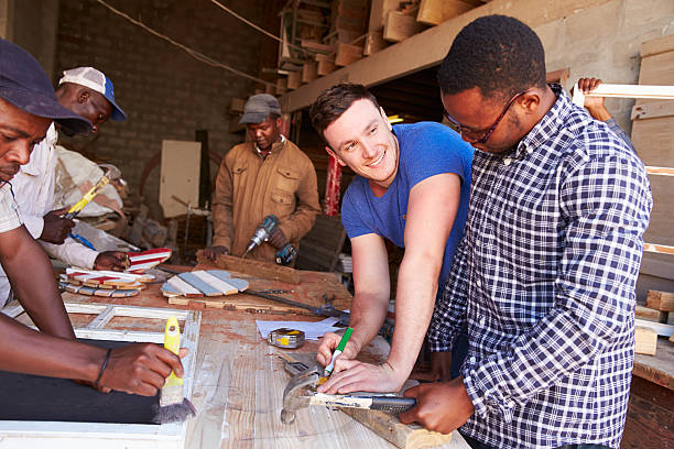 men at work in a carpentry workshop, south africa - community project stock photos and pictures