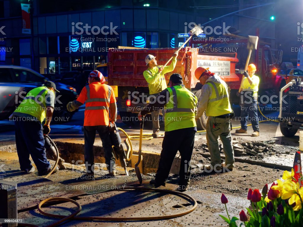 Men at work on the street at night in Manhattan stock photo