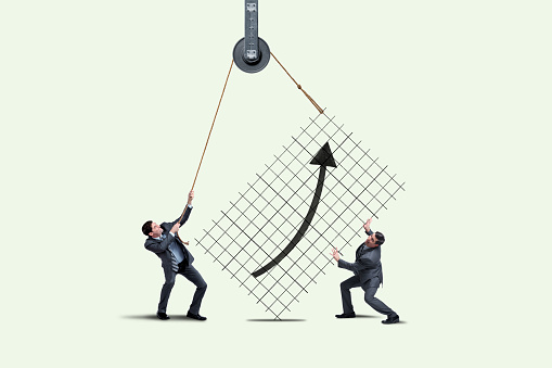 Two men apttempt to support the stock market by trying to lift a chart.