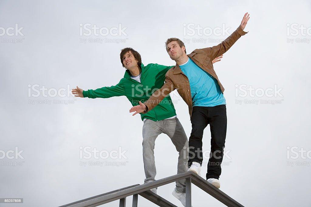 Men balancing on railings royalty-free stock photo