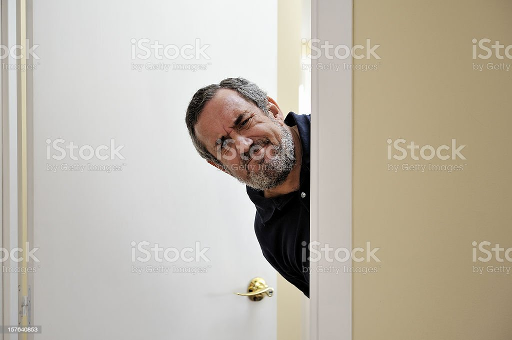 Men behind doorframe stock photo