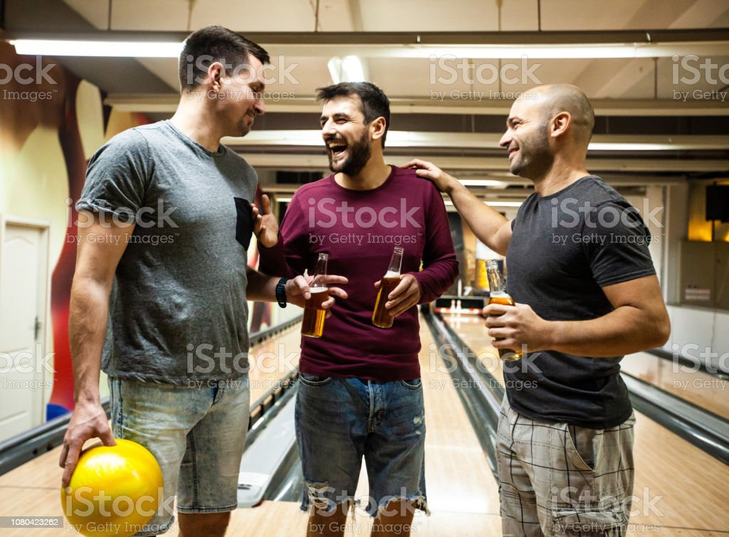 Men bowling and having beer in bowling alley stock photo