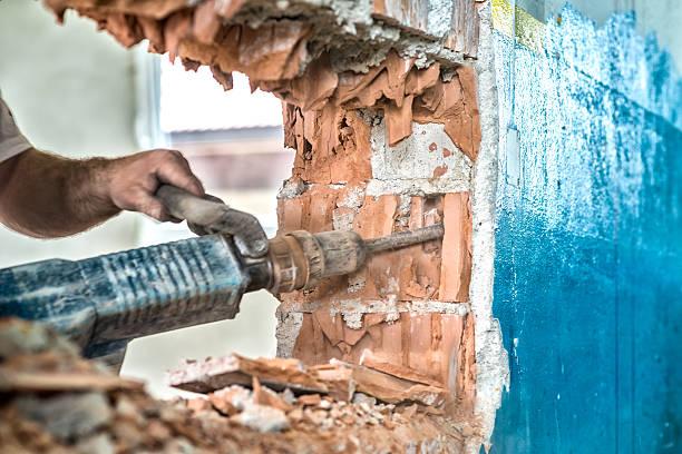 männer brechen wand mit einen presslufthammer - diy beton stock-fotos und bilder