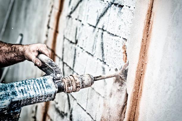 Men breaking wall using a jackhammer stock photo