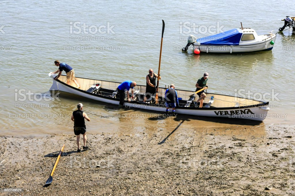 Men bringing ashore a four-man rowing boat at Appledore in Devon UK stock photo