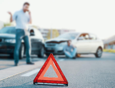 istock Men calling first aid after a bad car crash on the road 1047082714