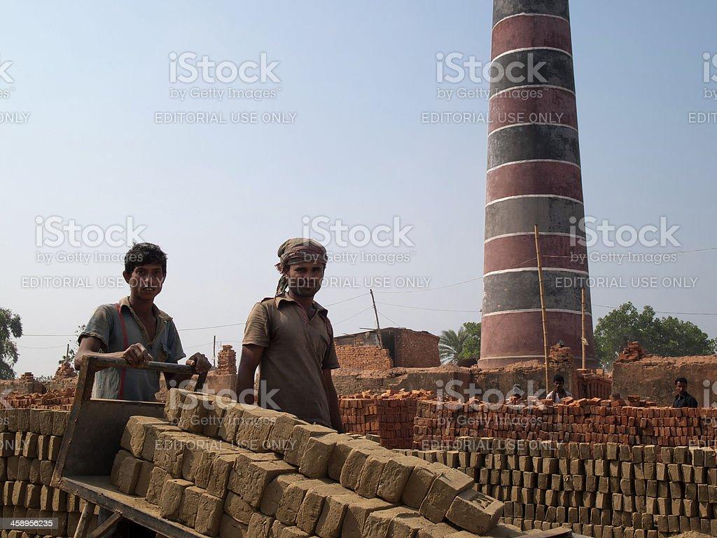 Men carrying bricks at a Brick factory in Bangladesh stock photo