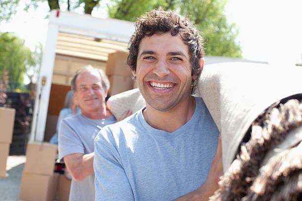 männer tragen teppich von moving van - teppich englisch stock-fotos und bilder