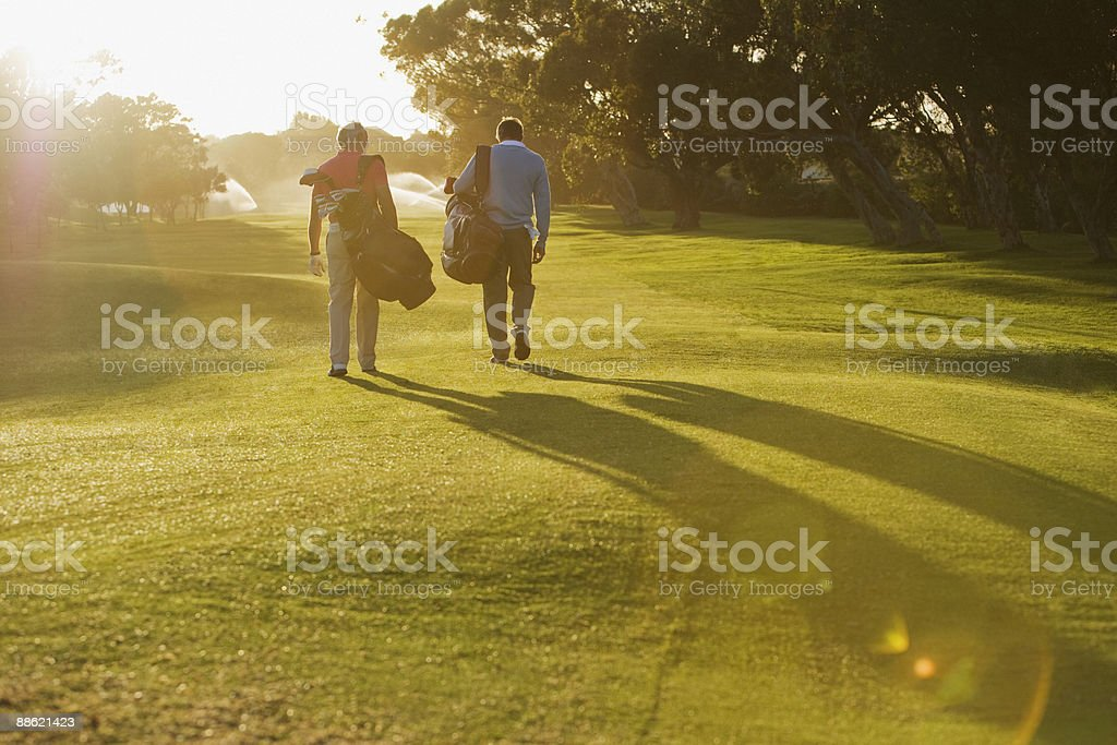 Men carrying golf bags on golf course stock photo