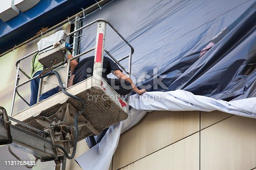 istock men change an advertising poster on the street standing on the tower of the crane 1131758433