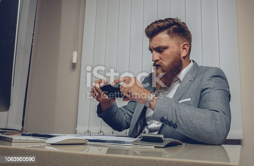 Men checking his smartphone at office, sitting at desk with computer