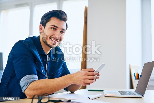 istock Men checking his smartphone at office, sitting at desk with laptop computer 666890114