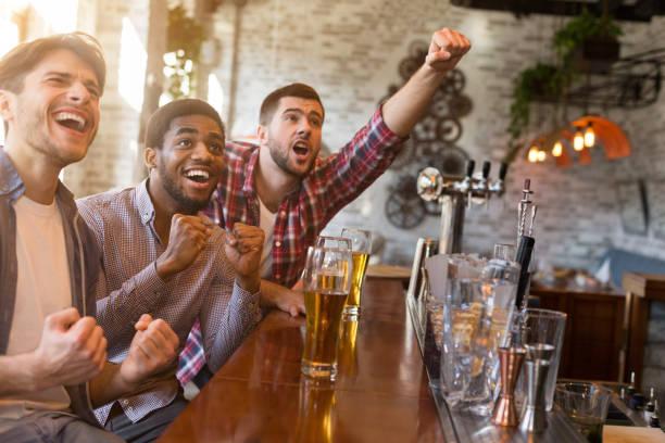 mannen juichen voor voetbalteam in de sport bar - group of fans talking stockfoto's en -beelden
