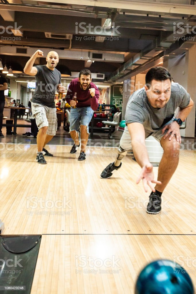Men cheering for their friend in the bowling alley stock photo
