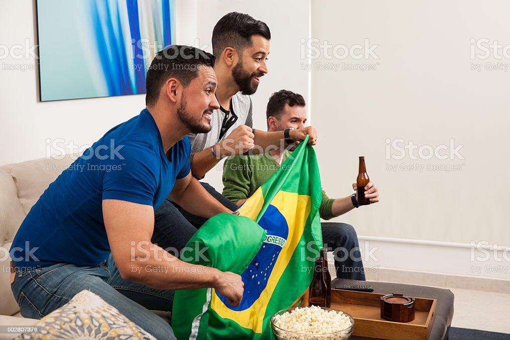 Homens torcendo com Bandeira Brasileira - foto de acervo