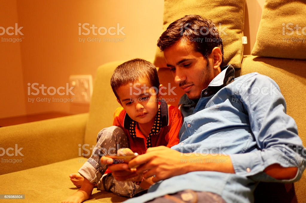 Men & child using mobile phone stock photo