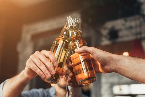 Men clinking bottles of beer together in bar
